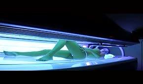 Poniéndose morena desnuda en el solárium