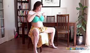 Una madura británica juega con sus tetas