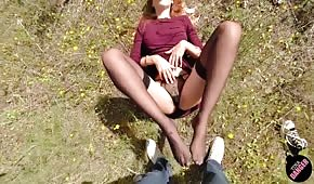 La chica masajea la polla con los pies al aire libre